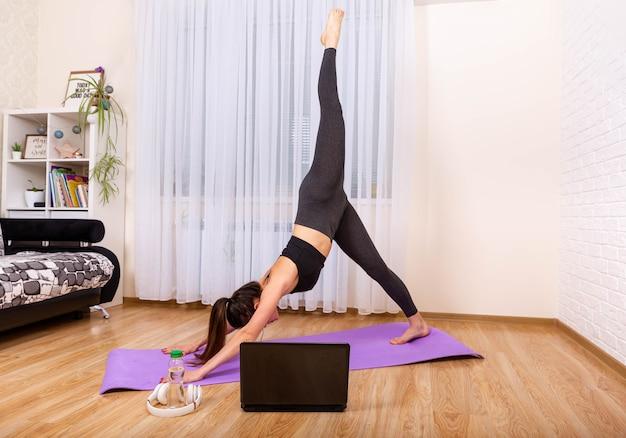Meisje kijken naar online lessen op laptop beoefenen van yoga meditatie