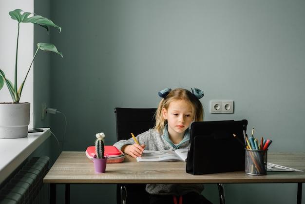 Meisje kijken naar videolessen op haar tablet en schrijven in haar notitieblok