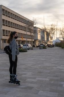 Meisje kijkend naar de horizon met schaatsen op de boulevard in palma de mallorca, spanje