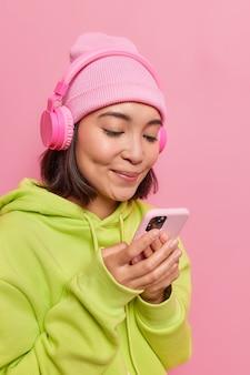 Meisje kijkt aandachtig naar het scherm van de smartphone luistert naar de audiotrack in een koptelefoon, nonchalant gekleed in roze, verslaafd aan moderne technologieën