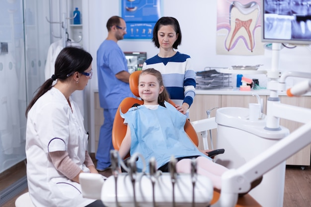 Meisje kijkt blij naar tandarts na professionele tandholtebehandeling in tandartspraktijk. kind met haar moeder tijdens tandencontrole met stomatolog zittend op een stoel.