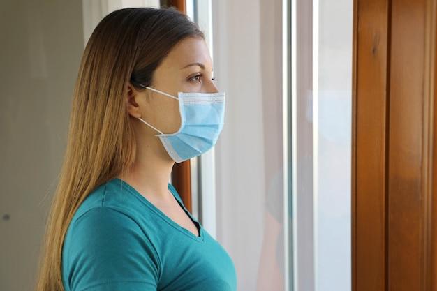 Meisje kijkt door het raam met chirurgisch masker tegen de ziekte van coronavirus 2019.