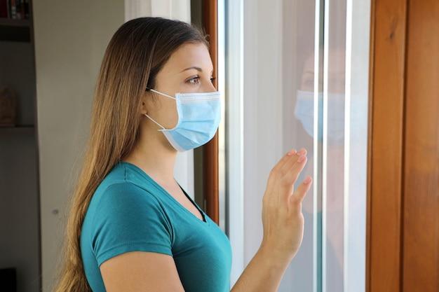 Meisje kijkt door het raam met masker tegen de ziekte van coronavirus 2019.