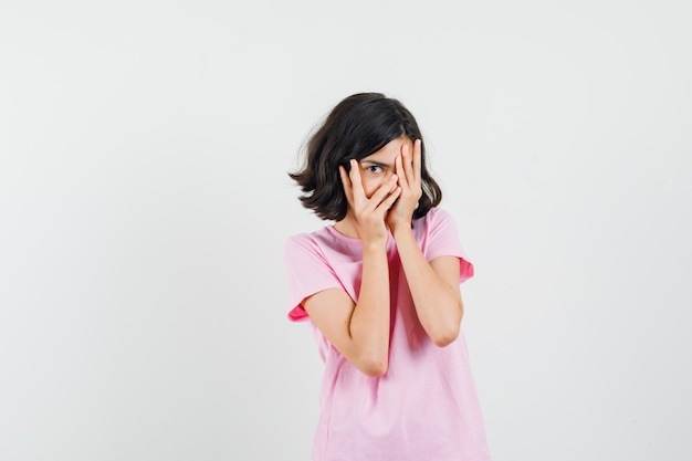 Meisje kijkt door vingers in roze t-shirt en kijkt nieuwsgierig, vooraanzicht.