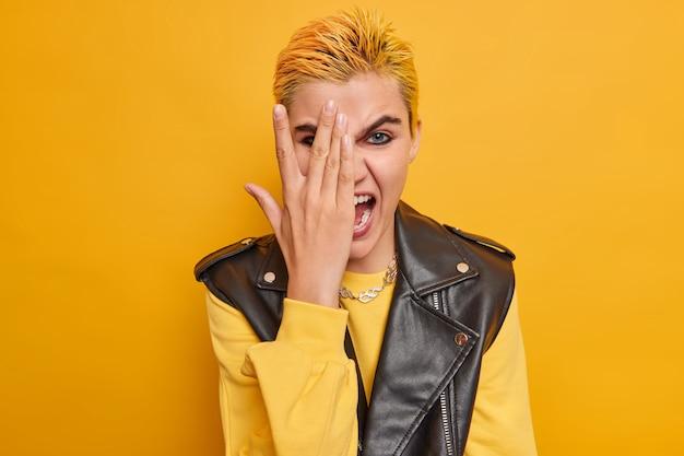 Meisje kijkt door vingers tegens gezicht met hand heeft trendy kapsel lichte make-up gekleed in casual jumper leren jas op geel heeft plezier binnenshuis