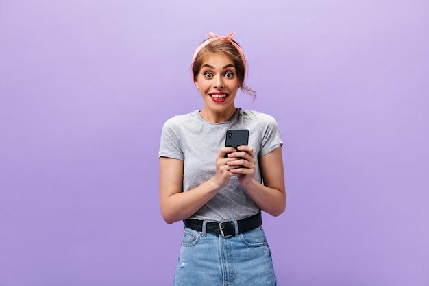 Meisje kijkt gelukkig en houdt smartphone vast. verrast jonge vrouw in grijs t-shirt en moderne rok op zoek naar camera op paarse achtergrond.