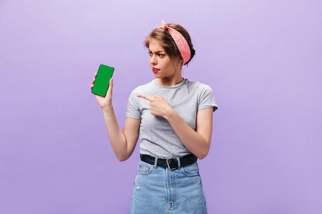 Meisje kijkt met misverstand op smartphone. moderne jonge vrouw in grijs t-shirt en denim rok met brede riem poseren.