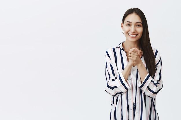 Meisje kijkt met zorgzame en bewonderenswaardige ogen, opgewonden en gecharmeerd van een aangenaam geschenk, handen over de borst geklemd en glimlachend van geluk, staande in gestreepte blouse over grijze muur