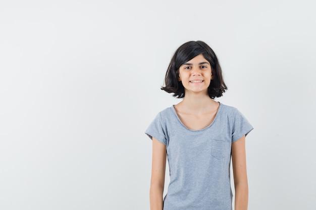 Meisje kijkt naar camera in t-shirt en ziet er mooi uit. vooraanzicht.