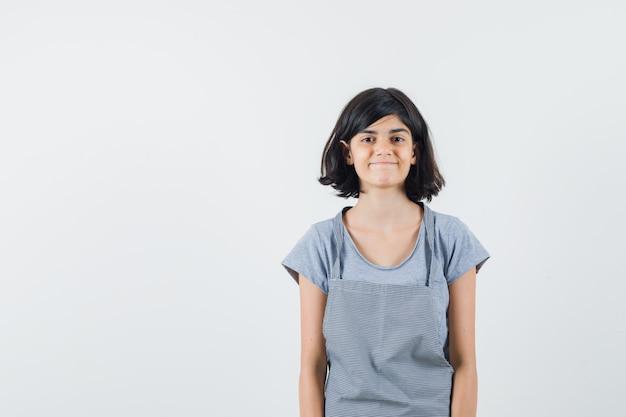 Meisje kijkt naar camera in t-shirt, schort en kijkt vrolijk, vooraanzicht.