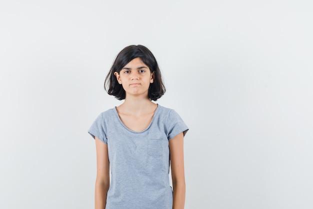 Meisje kijkt naar de camera in t-shirt en kijkt verstandig, vooraanzicht.