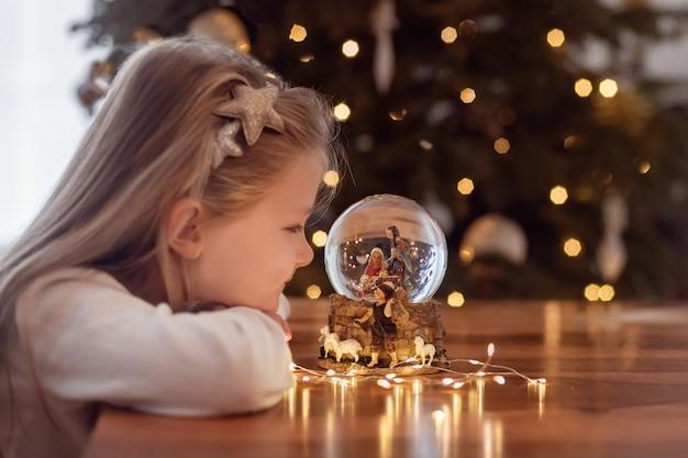 Meisje kijkt naar een glazen bol met een scène van de geboorte van jezus christus in een glazen bol op een kerstboom