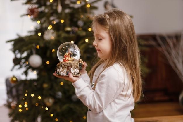 Meisje kijkt naar een glazen bol met een scène van de geboorte van jezus christus in een glazen bol