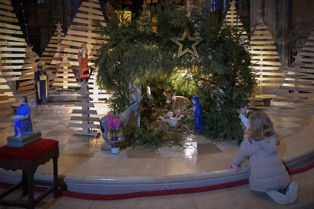 Meisje kijkt naar een kerststal met baby jesus creche
