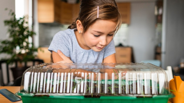 Meisje kijkt naar gewassen groeien thuis