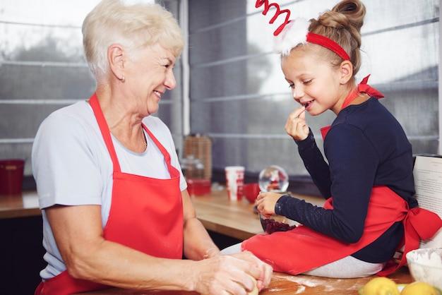 Meisje kijkt naar haar grootmoeder deeg maken