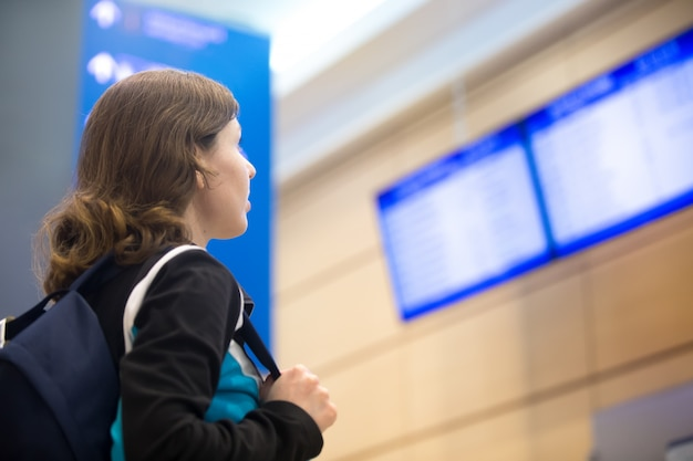Meisje kijkt naar luchthaven vlucht informatie board