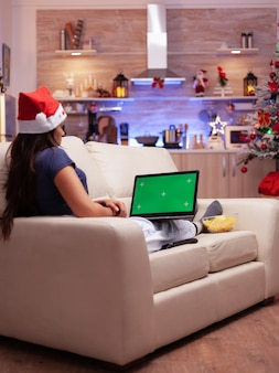 Meisje kijkt naar mock-up groen scherm chroma key laptop met geïsoleerde display