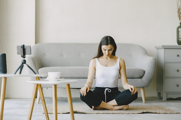 Meisje kijkt naar telefoon. yogi kneden. vrouw thuis in een sportkleren.