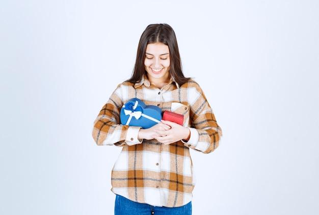 Meisje kijkt naar twee geschenken en staat op een witte muur.