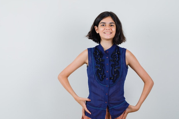 Meisje kijkt naar voorkant in blauwe blouse, rok en kijkt vrolijk.