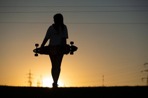 Meisje kijkt naar zonsondergang met een longboard in haar hand