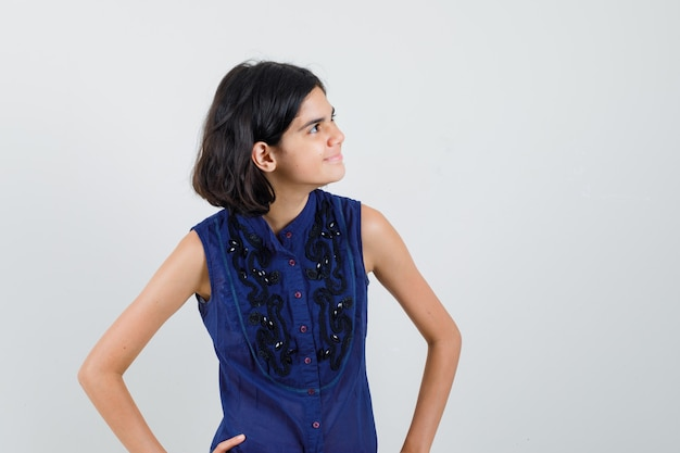 Meisje kijkt opzij in blauwe blouse en kijkt vrolijk.
