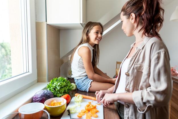 Meisje kijkt toe terwijl moeder het diner klaarmaakt
