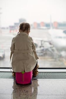 Meisje kijkt uit het raam naar de luchthaventerminal