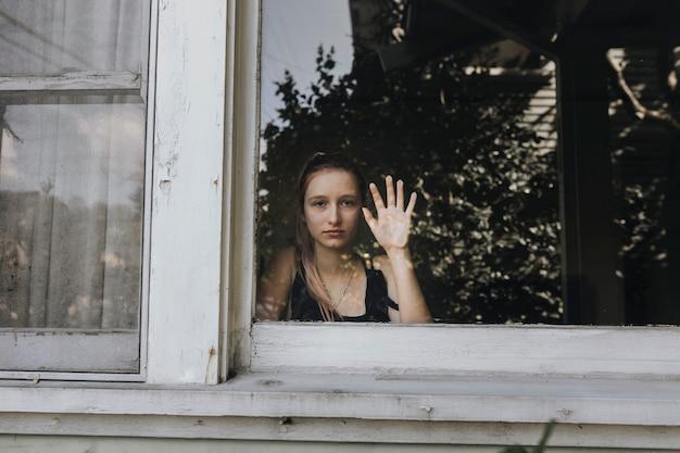 Meisje kijkt uit het raam van haar huis in la tijdens de covid-19 pandemie