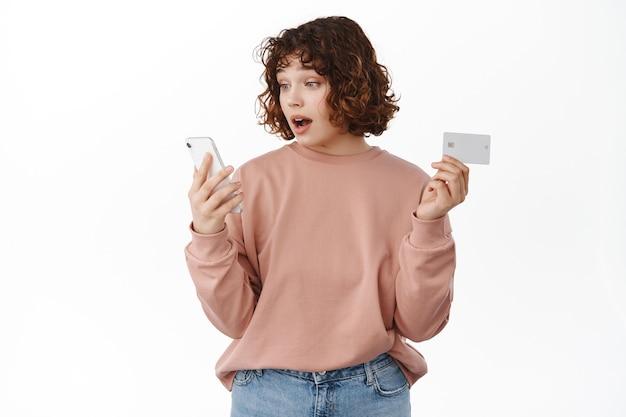 Meisje kijkt verbaasd naar het scherm van de mobiele telefoon terwijl ze online winkelt, een creditcard vasthoudt, betaalt voor levering via internet, een goede prijs in de winkel ziet, op wit staat