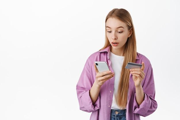 Meisje kijkt verbaasd naar het smartphonescherm terwijl ze betaalt voor online boodschappen, creditcard vasthoudt, app-melding op mobiele telefoon leest tijdens aankoop, over witte muur staat