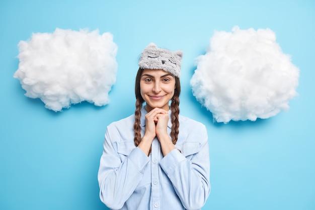 Meisje kijkt zelfverzekerd naar camera houdt handen onder kin glimlacht zacht draagt zacht slaapmasker en casual shirt geïsoleerd op blauw
