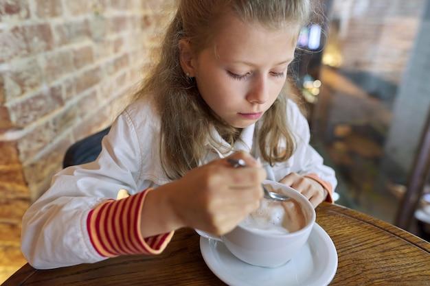 Meisje kind 9, 10 jaar oud met kop warme chocolademelk zittend in café aan tafel.