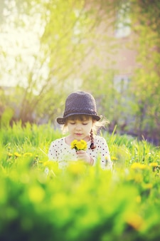 Meisje, kind, bloemen paardebloemen in de lente speelt. selectieve aandacht.