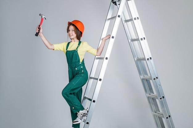 Meisje kind dragen uniform en helm tijdens het werken in werkplaats met hamer op ladder, carrière.