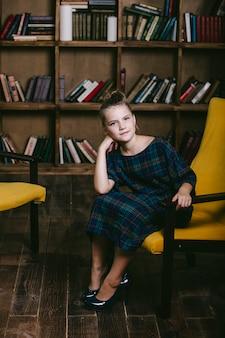 Meisje kind in de bibliotheek met boeken op een strikte manier houdt zich bezig met onderwijs en opleiding