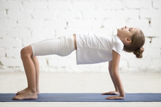 Meisje kind in omgekeerde tabel top pose, witte studio achtergrond
