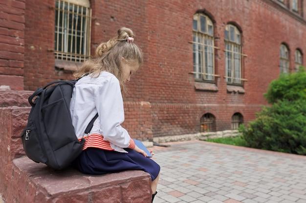 Meisje kind in uniform met rugzak zittend op schoolplein lezen notebook, kopieer ruimte. terug naar school, start van lessen, onderwijs, kennis, lessen, kinderconcept