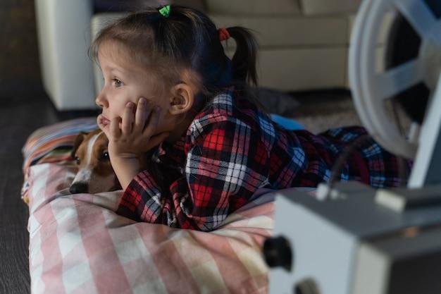 Meisje kind kijken naar een oude film op een retro vintage filmprojector met een hond