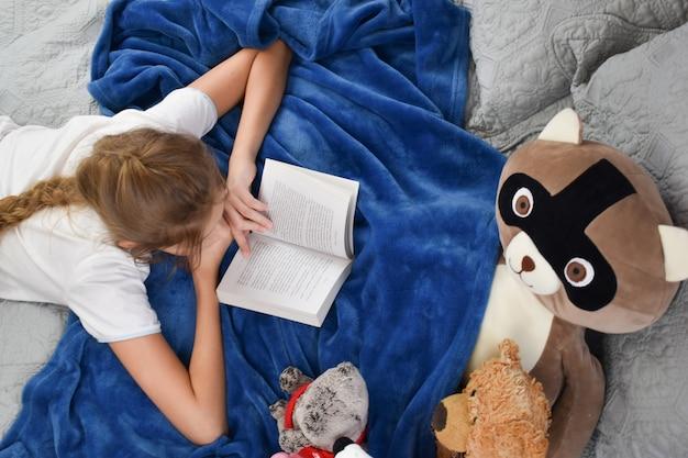 Meisje kind ligt op het bed met een boek en speelgoed