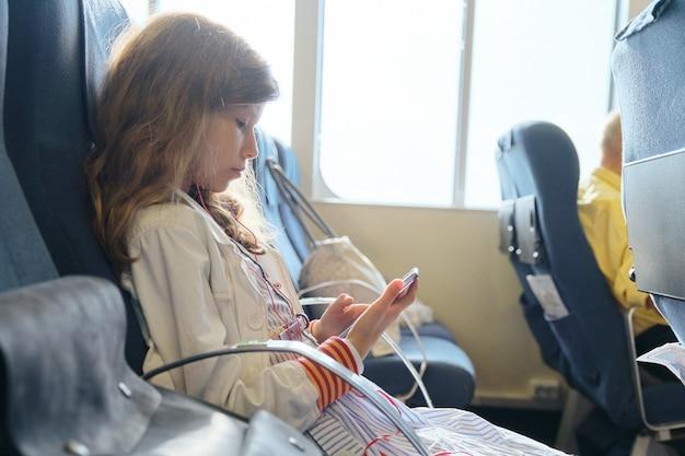 Meisje kind met behulp van smartphone zittend in de veerboot. reizen, toerisme, vervoer over water