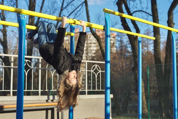 Meisje kind opknoping ondersteboven op buitensporten speeltuin met gesloten ogen