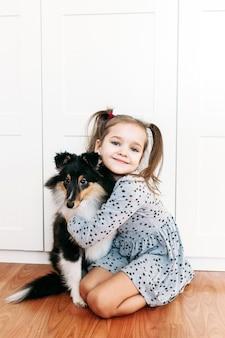 Meisje, kind speelt en traint haar hond thuis, puppy, dierentraining, vreugde, comfort, licht interieur