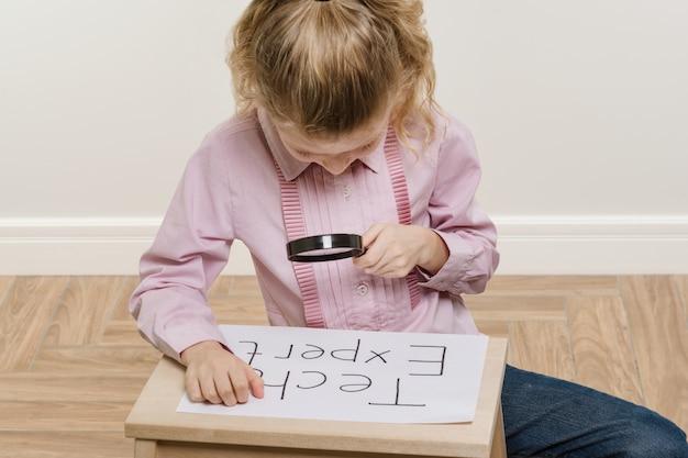 Meisje kind stuk papier met een woord tech expert te houden.
