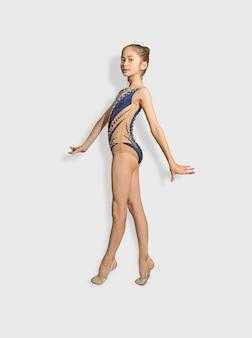 Meisje kind turnster kijken camera, oefenen geïsoleerd op een witte achtergrond. sport, training, ritmische gymnastiek, actief levensstijlconcept.