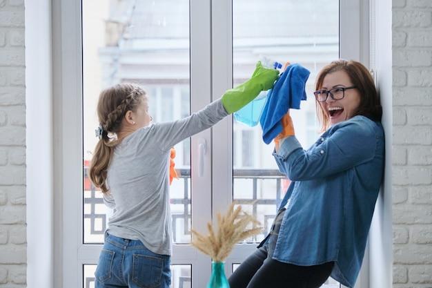 Meisje kind vrouw wassen ramen helpen, doe het schoonmaken thuis
