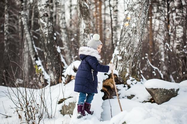 Meisje kind wandelen in het woud van de winter in een blauwe jas en grijze hoed