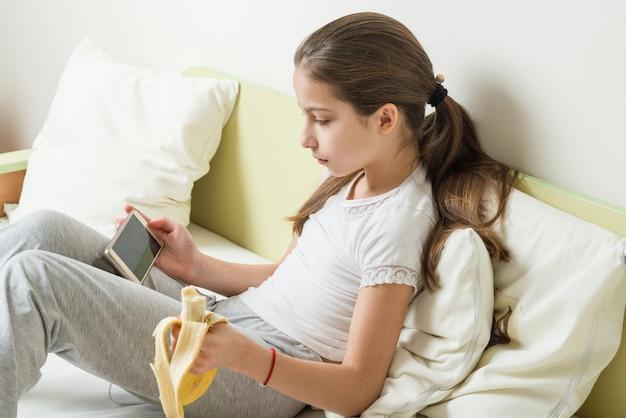 Meisje kind zit in bed lezen, kijken naar video in smartphone