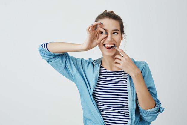 Meisje klaar om nieuwe horizonten te ontdekken. vrolijke mooie europese vrouw die ok gebaar over oog houdt en door het opzij kijkt, gezicht met wijsvinger raakt en in speelse stemming is